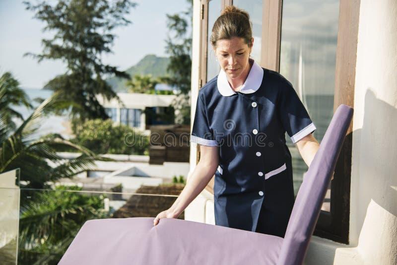 Hushållerska som gör ren ett hotellrum royaltyfri bild