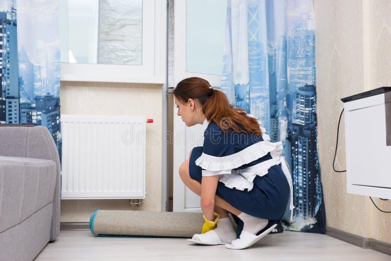 Hushållerska som kontrollerar termostaten på ett element royaltyfri bild