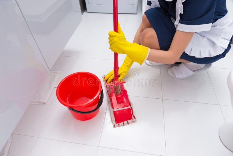 Hushållerska som passar en ren torkduk till en golvmopp royaltyfria bilder