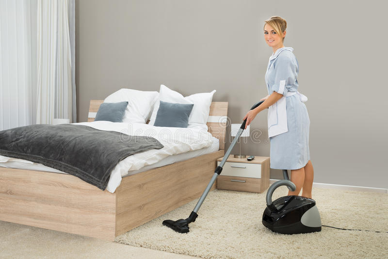 Hushållerskalokalvård med dammsugare royaltyfria bilder
