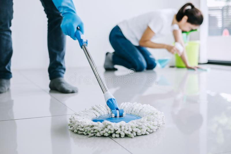 Hushållning och lokalvårdbegrepp, ungt par i blåa gummihandskar som torkar damm genom att använda golvmopp och dammtrasan, medan  fotografering för bildbyråer