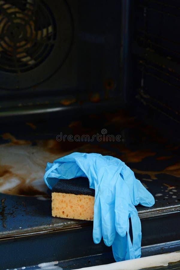 Hushållsarbete- och hushållningbegrepp Skurning av ugnen och av ugnen Gul svamp med tvåligt vatten och blåa gummihandskar royaltyfri foto