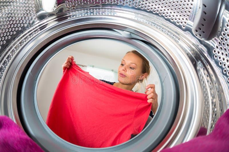 Hushållsarbete: ung kvinna som gör tvätterit royaltyfria bilder