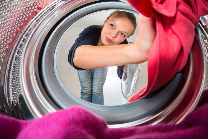 Hushållsarbete: ung kvinna som gör tvätterit arkivbild