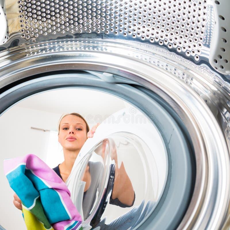 Hushållsarbete: ung kvinna som gör tvätterit fotografering för bildbyråer
