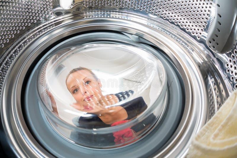 Hushållsarbete: ung kvinna som gör tvätterit royaltyfri fotografi