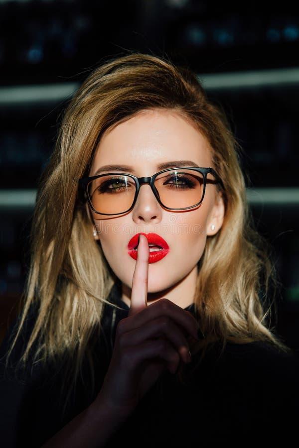 hush Женщина в стеклах просит безмолвие или засекреченность с пальцем на красных губах shh жест рукой стоковые фотографии rf