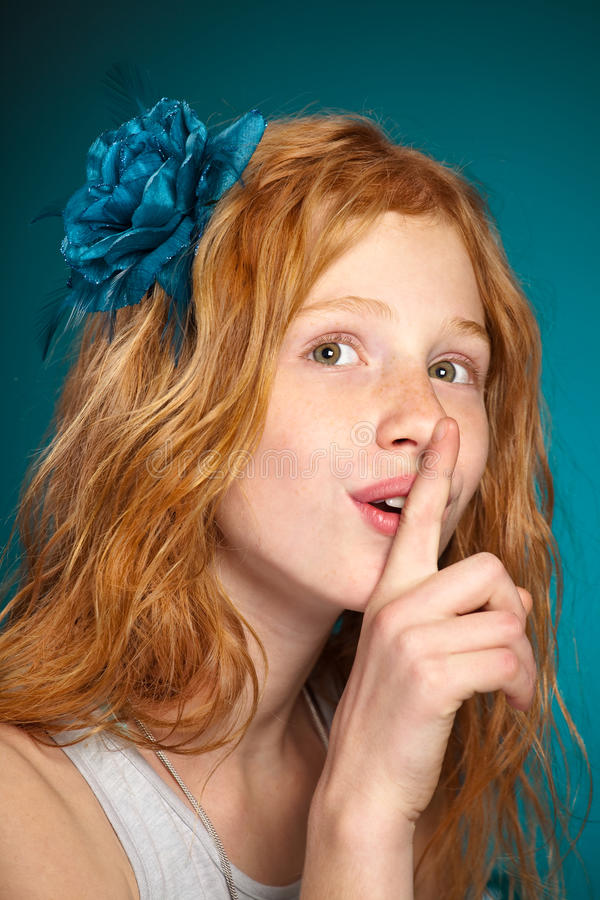 Hush. Portrait of a young beautiful girl with finger to her lips stock photos