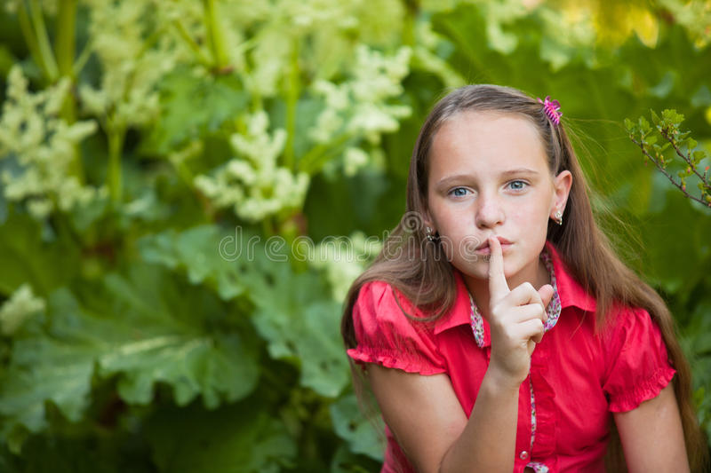 Hush, it is a secret. Shh. secret - Beautiful young girl with her finger over her mouth, hushing royalty free stock photography