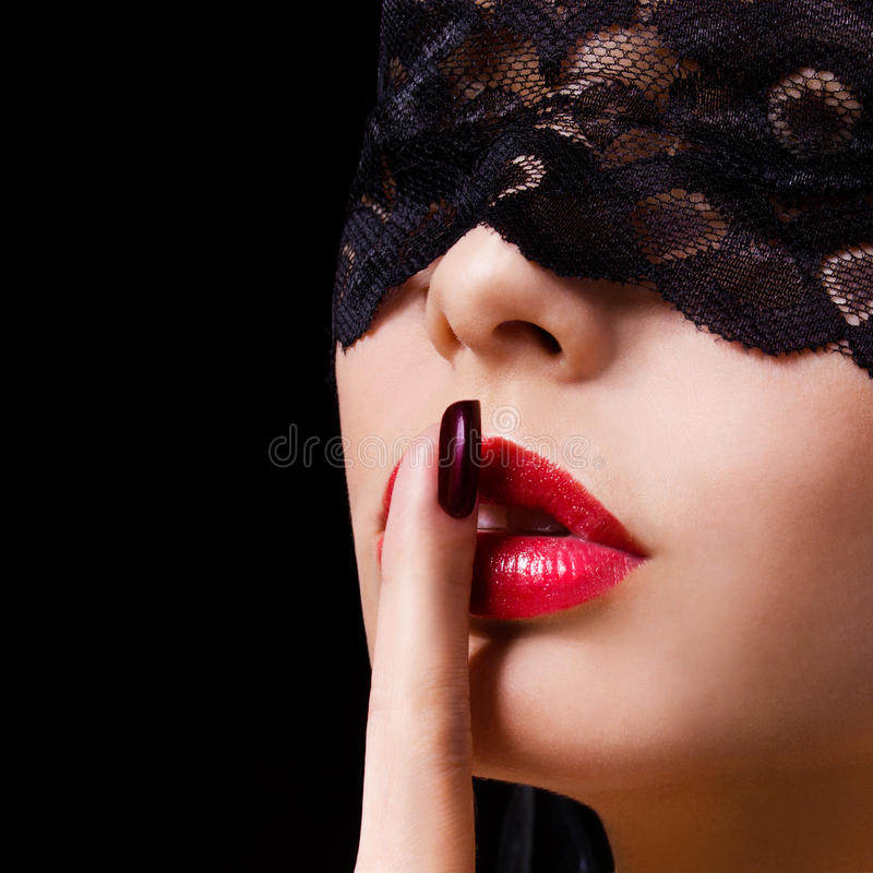 Hush. woman with finger on her red lips showing shush. Erotic girl with lace mask over black. Background stock images