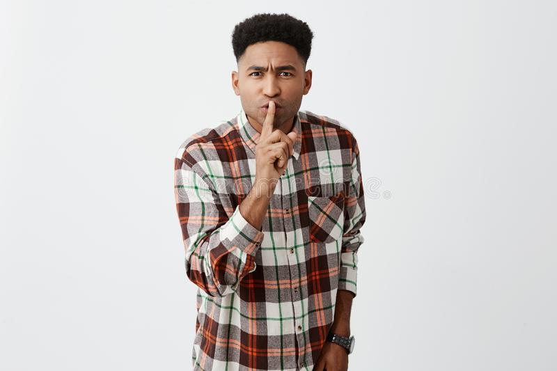 Hush. You`re in library, not at home. Young good-looking dark-skinned male student holding index finger in front of lips royalty free stock photography
