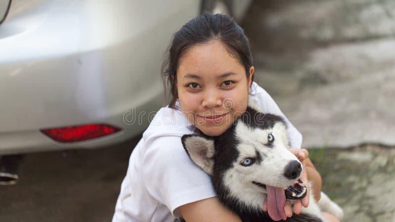 Husky siberiano del abrazo de las mujeres imagen de archivo