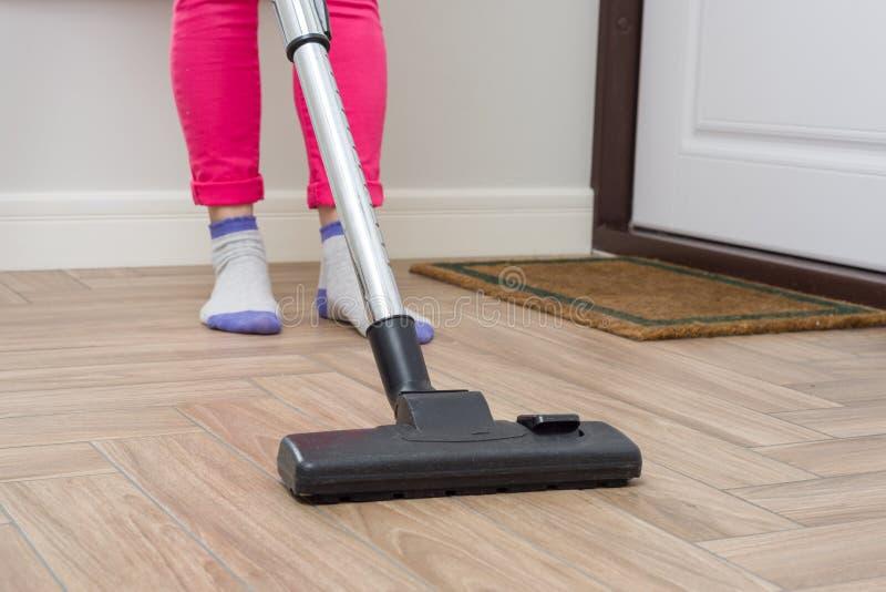 Huslokalvård Kvinnan gör ren genom att använda dammsugare royaltyfria foton