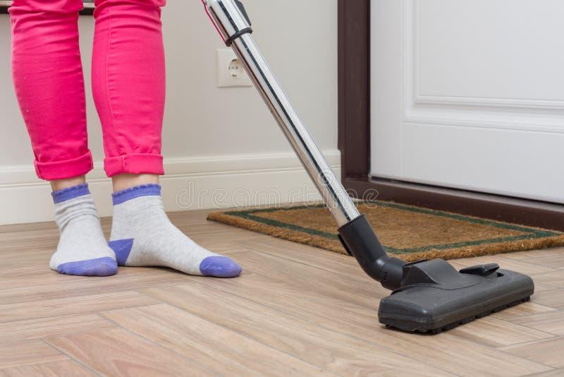Huslokalvård Kvinnan gör ren genom att använda dammsugare royaltyfri fotografi