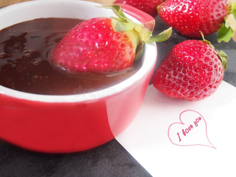 Husmanskost nya saftiga jordgubbar med smältt mörk choklad royaltyfri bild