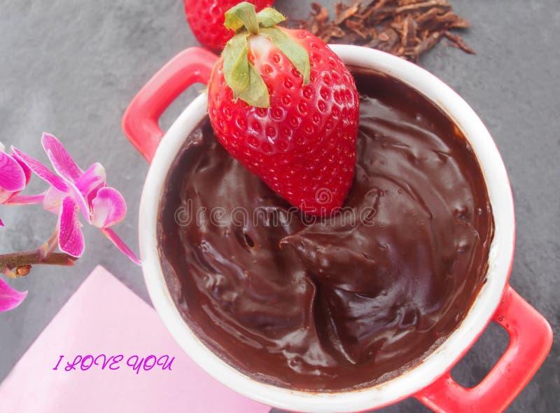 Husmanskost nya saftiga jordgubbar med smältt mörk choklad arkivbilder