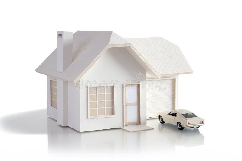 Husminiatyr med bilen som isoleras i vit bakgrund för fastighet- och konstruktionsbegrepp Planlagd husminiatyr och crea royaltyfri foto