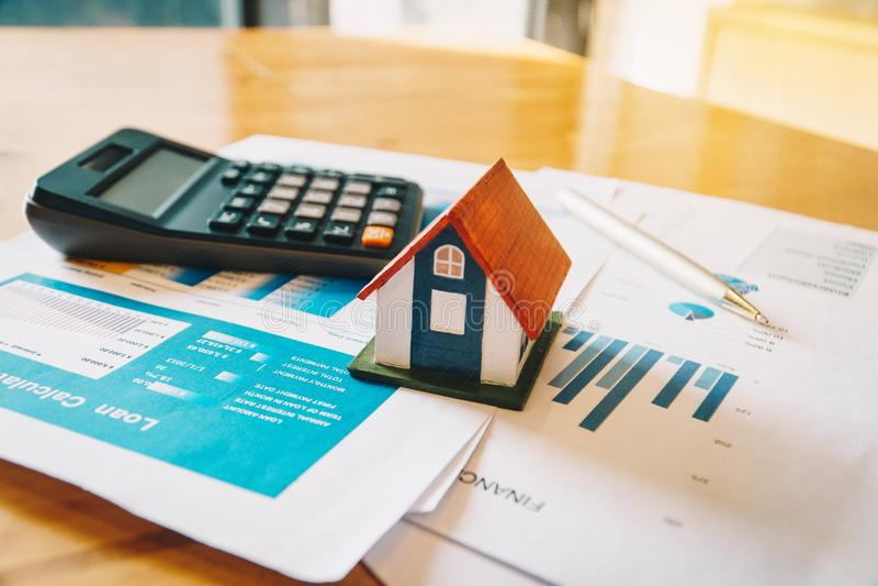 Husmodell, räknemaskin och finansiellt diagram på trätabellen Investering till det köpande egenskapsbegreppet royaltyfri foto