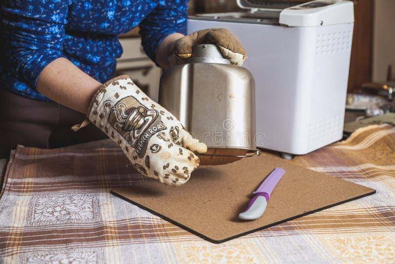 Husmor drar ut nytt bröd från den elektriska brödmaskinen för formen arkivbild