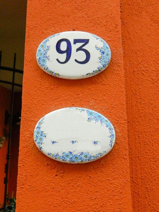 Husnummer, keramisk platta med blåa siffror, blommor och namnet av gatan Dekorativt tecken för för gatahusnamn eller nummer royaltyfri fotografi