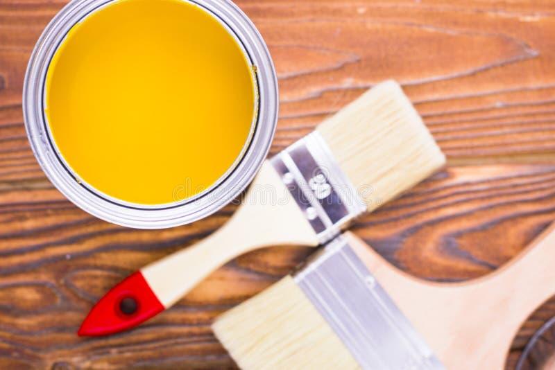 Husrenoveringbegreppet, colorfull målar på burk och målarpenslar på mörk träbakgrund royaltyfria foton