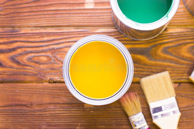 Husrenoveringbegreppet, colorfull målar på burk och målarpenslar på mörk träbakgrund royaltyfria bilder
