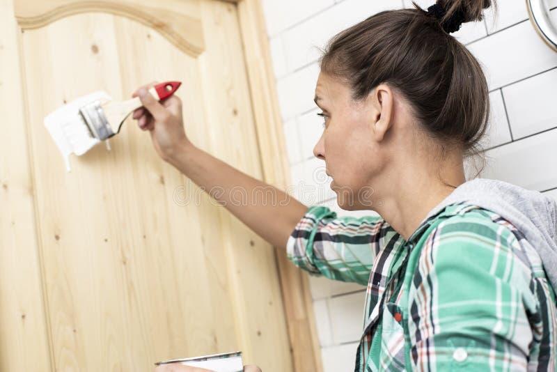 Husreparation Kvinnan målar en trädörr i badrummet i whit arkivfoton