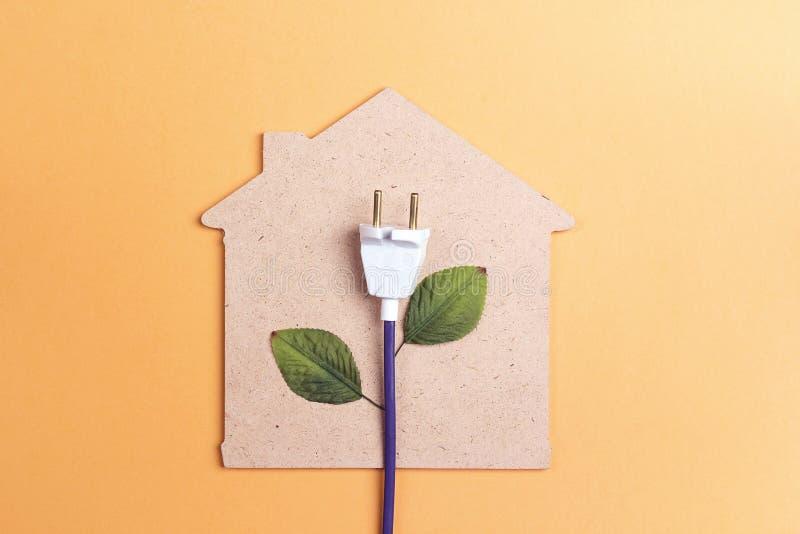 Hussymbol med proppen som en växt pengar för holdingen för kulabegreppsenergi sparar kvinnabarn fotografering för bildbyråer
