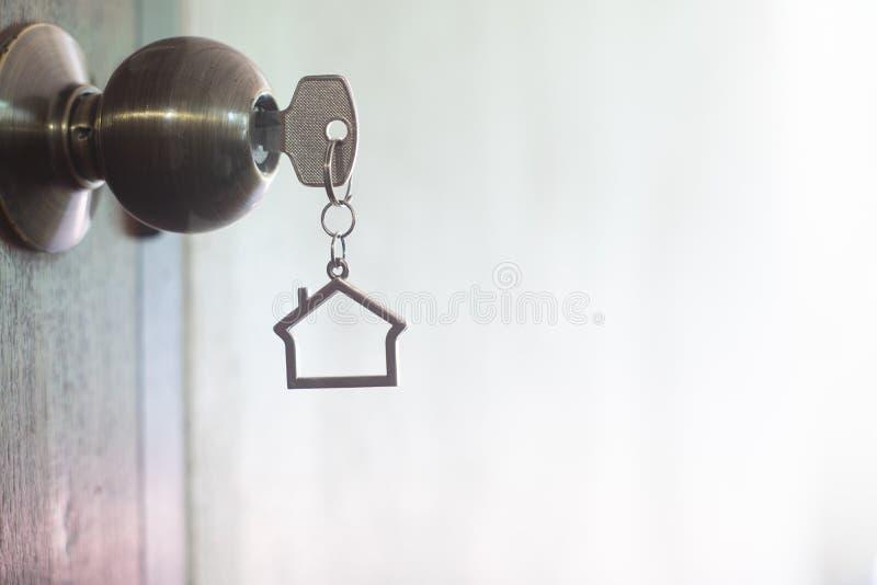 Hustangent med den hem- keyringen i nyckelh?l p? tr?d?rr arkivfoto