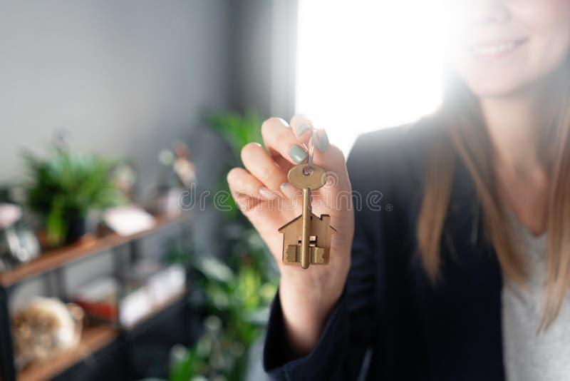 Hustangenten roterar på fingret i kvinnans händer Unga nätta kvinnaleenden Modern ljus lobbyinre f?r delshus f?r gods f?rs?ljning arkivfoto