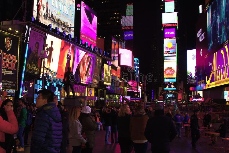 Hustle and Bustle of Times Square, New York City. Crowds gather in the heart of NYC in downtown Manhattan. Brightly lit billboards and advertisements surround royalty free stock images