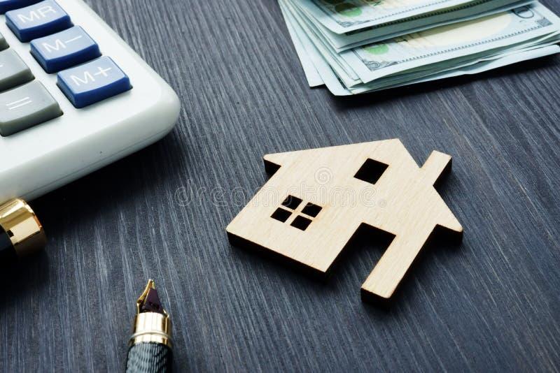 Husvärde Modell av hemmet på ett mörkt trä med räknemaskinen och pengar arkivbilder