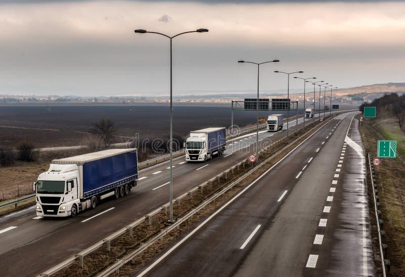 Husvagn eller eskortfartyg av lastbilar på en våt landshuvudväg arkivbilder