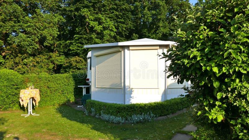 Husvagn med en fast veranda som göras av markistyg, glass glidningsfönster och rullgardiner på en tysk campingplats arkivbild