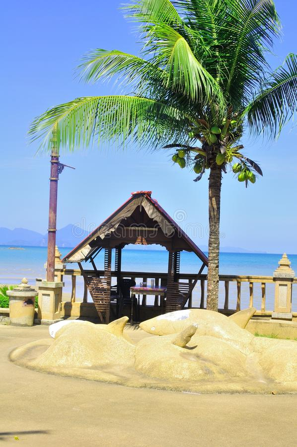 A hut by the beach. Panorama of a hut under the shades of a palm tree by the beach royalty free stock image
