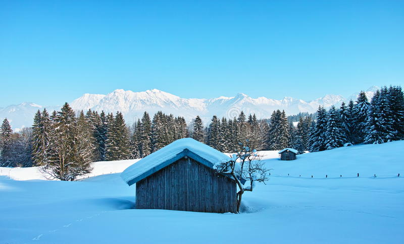 Rural shed in snowy alpine landscape by blue sky royalty free stock images