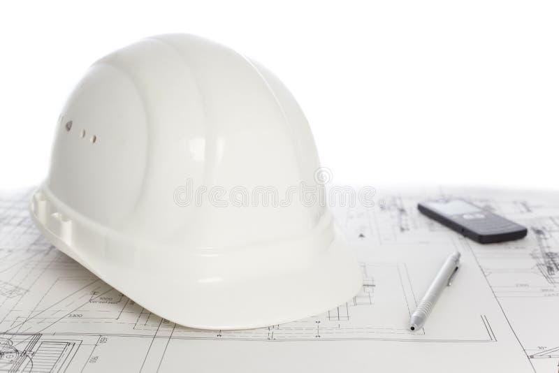 Hut, Handy und Stift im Bauplan lizenzfreies stockbild
