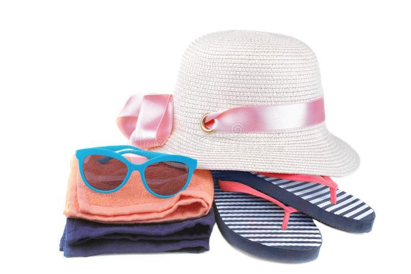 Hut mit Flipflops in einem blauen und weißen Streifen nahe bei einem orange und blauen Tuch und blauen Gläsern Getrennt stockfotos