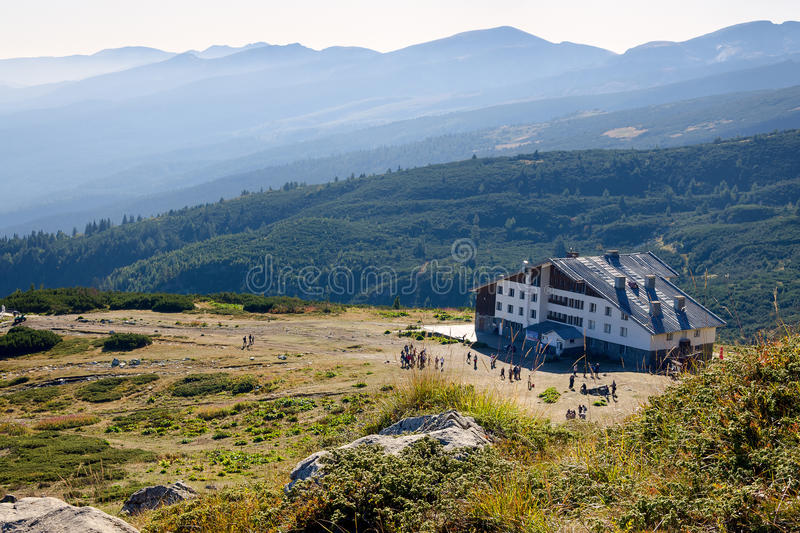 Hut in the mountains. `Rilski ezera` hut and group of people heading to seven Rila lakes. This is the staring point for one of the most popular tourist routes in royalty free stock photos