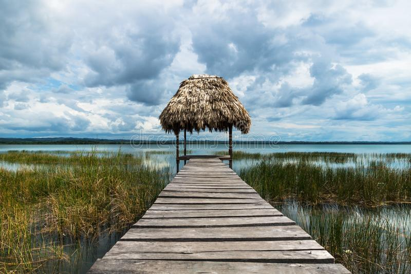 Hut with straw roof at the dock along the lake shore with dark blue cloudscape, El Remate, Peten, Guatemala royalty free stock photo