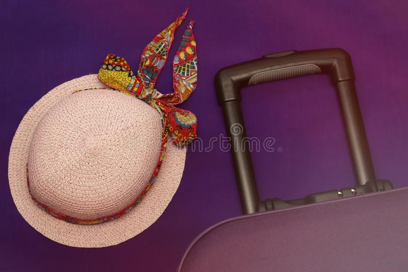 Hut und Koffer auf einer lila Hintergrundtourismusreise stockfoto