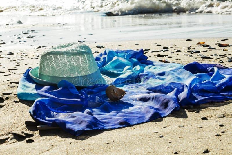 Hut- und Strandkittel auf dem Strand mit dem Meer im Hintergrund stockfotografie