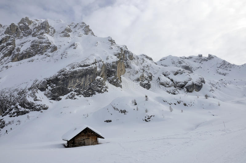 Hut under collac peak, dolomites. Scenic landscape of a hut with peak in background in winter under high snow, shot in cloudy bright light stock photo