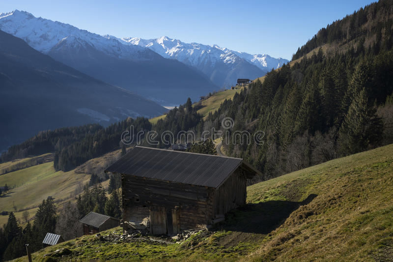 Hut with a view on the snowy mountains, Tirol Austria. Hut on green gras with a view on the snowy mountains, Tirol Austria, Pass Thurn stock images