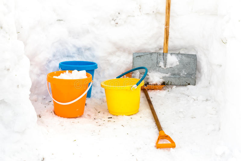 Hut with walls of snow and colorful buckets plus snowplow royalty free stock image