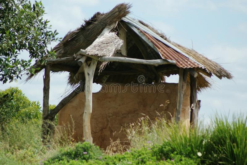 Lean To Hut. The hut was not constructed very well and is sure to fall to the ground. The tin on the roof will blow away in a windstorm. It is a shelter for royalty free stock photos