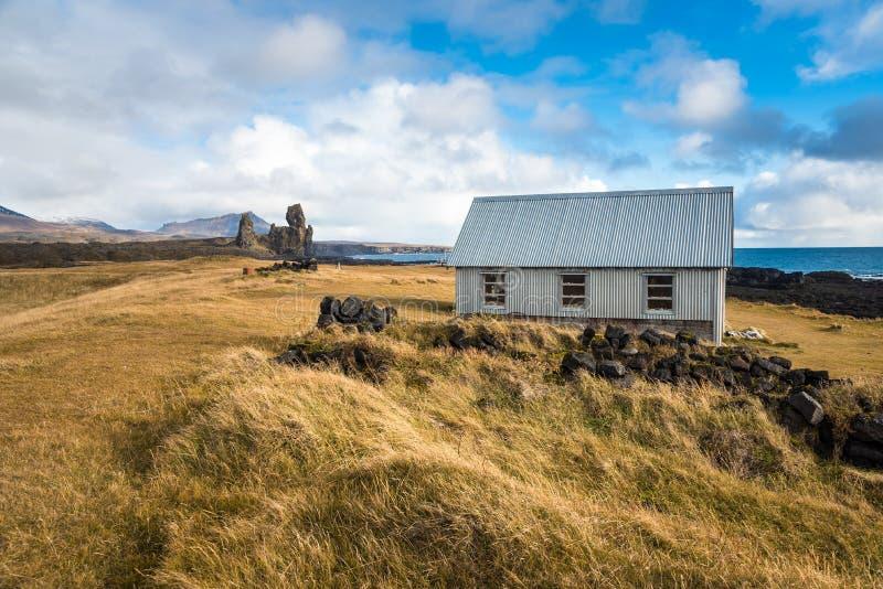 Hutin um prado ao longo de Rocky Coast de Islândia e do céu azul fotografia de stock royalty free