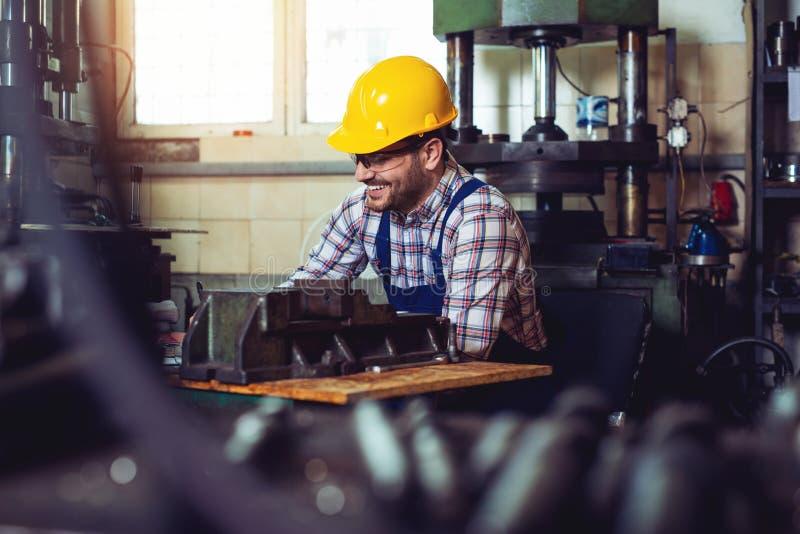 Hutnictwo pracownik szczęśliwie pracuje w jego warsztacie z zbawczym hełmem dalej zdjęcia royalty free