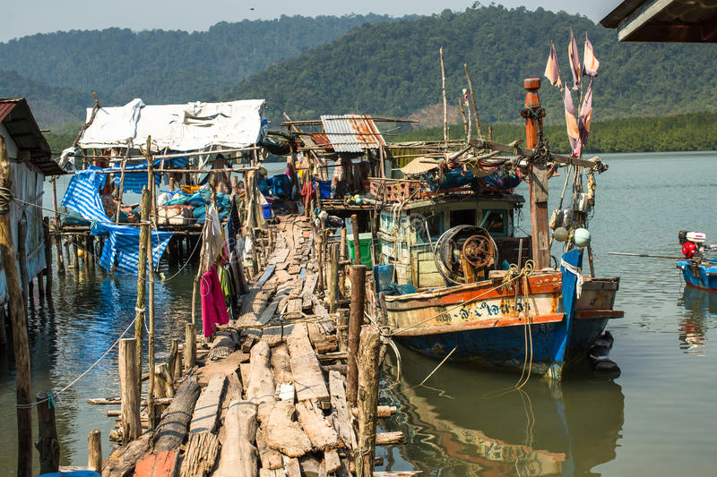 Huts and fishing boat at the pier in at fisherman village. KOH CHANG, THAILAND - FEB 4, 2016: Huts and fishing boat at the pier in at fisherman village. In stock photos