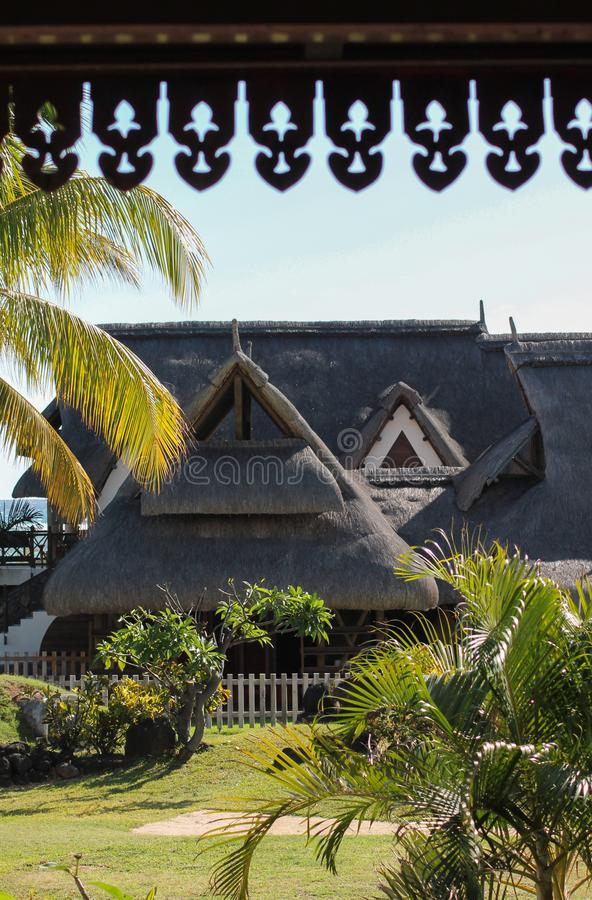 Traditional building in modern settings. Huts with thatched roofs, made of the fiber from sugar cane plants. At a hotel in Mauritius royalty free stock images